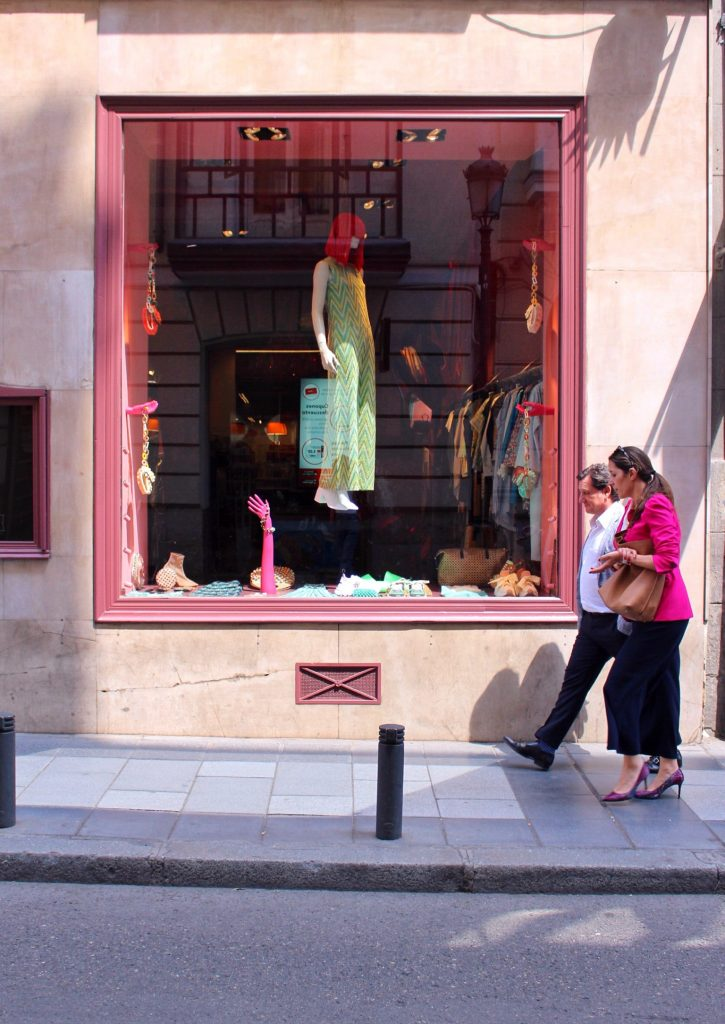 A couple walking infront of a shop